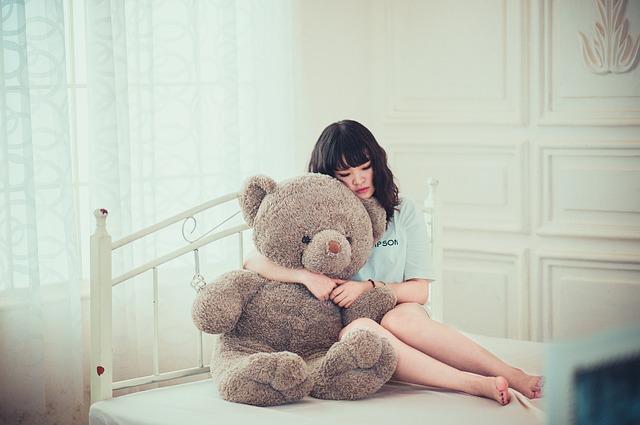 Žena s veľkým plyšovým medveďom sediaca na posteli.jpg