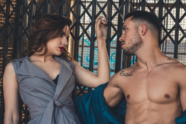 Muž s vyzlečenou košeľou sa túžobne pozerá na ženu v sivých šatách.jpg