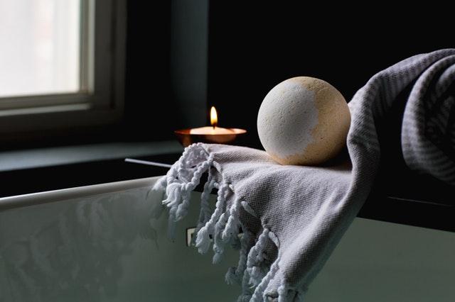Šatka, sviečky a guľa do kúpeľa položené na poličke.jpg
