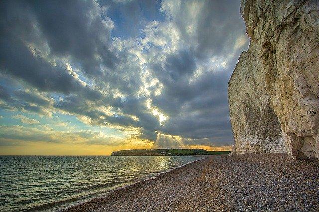 Skalný útes na pláži pri mori a slnko prenikajúce cez oblaky.jpg