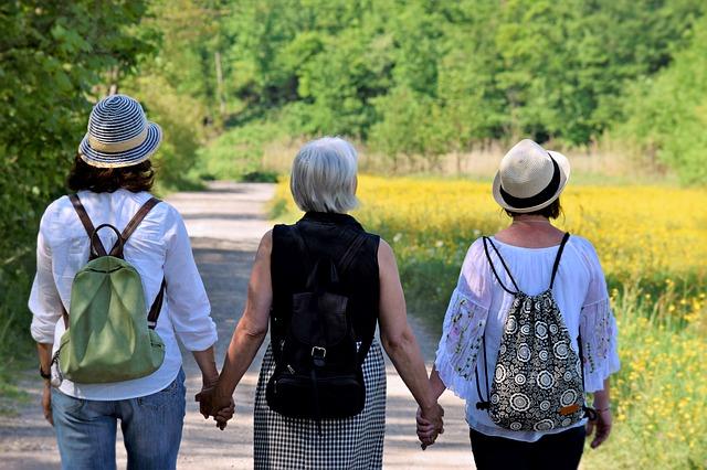 Tri staršie ženy sa držia za ruky a kráčajú po chodníku v prírode.jpg