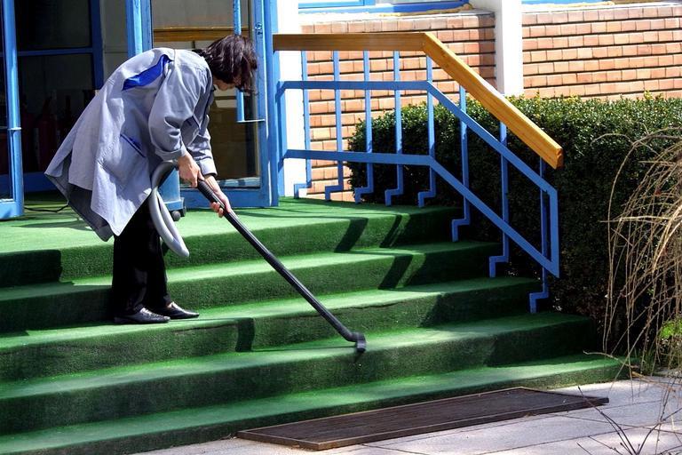 Žena vysáva schody, upratovanie