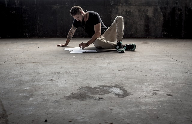 Muž sedí na podlahe a kreslí na papier