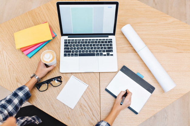 picture-work-stuff-table-hands-young-woman-working-with-laptop-holding-cup-coffee-notebooks-black-glasses-hard-working-success-graphic-design_197531-1861